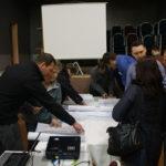 Mehrere Personen über Planungskarten gebäugt, diskutierend