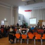 Veranstaltungssaal, Teilnehmer fotografiert von hinten Richtung Bühne