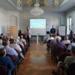 Blick in den Saal, Teilnehmer, dahinter Referenten